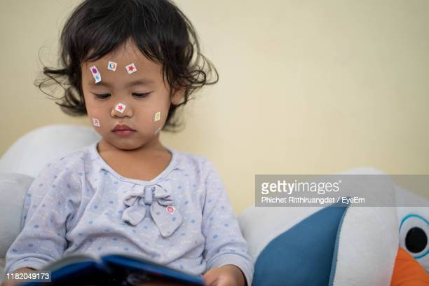 cute girl with stickers on face at home - phichet ritthiruangdet stock photos and pictures