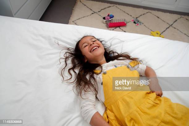 cute girl with wavy hair collapsed on bed laughing - long bright yellow dress stock pictures, royalty-free photos & images