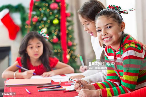 Cute girl works on Christmas crafts with friends