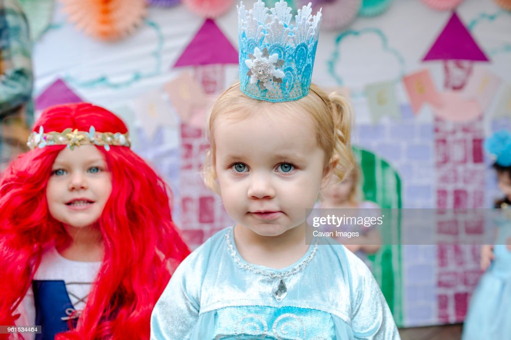 cute girls against castle painting during princess party stock photo