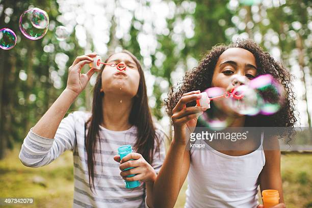 cute girls blowing bubbles outdoors - pre adolescent child stock pictures, royalty-free photos & images