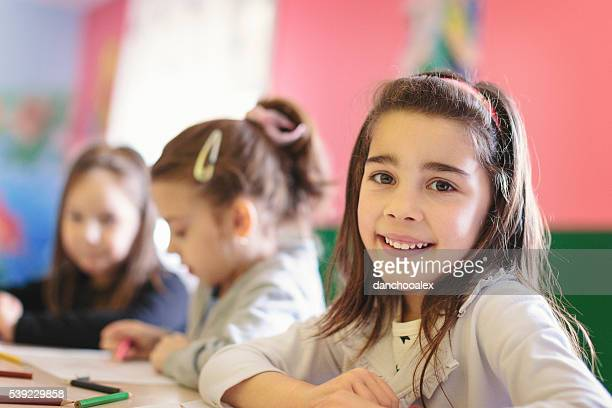 Cute girls in the classroom drawing and smiling for camera
