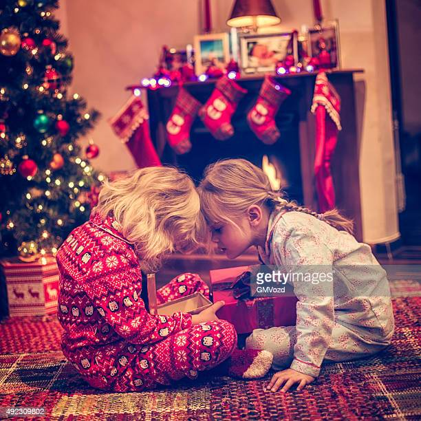 Cute Girls Opening Presents in in front of Christmas Tree