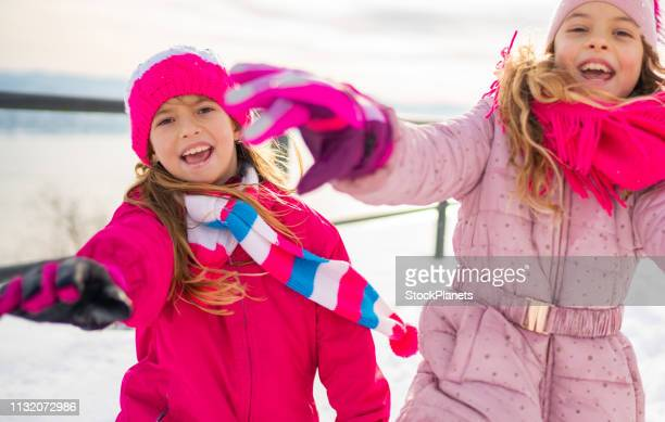 cute girls running for camera on winter outdoors - girls flashing camera stock pictures, royalty-free photos & images