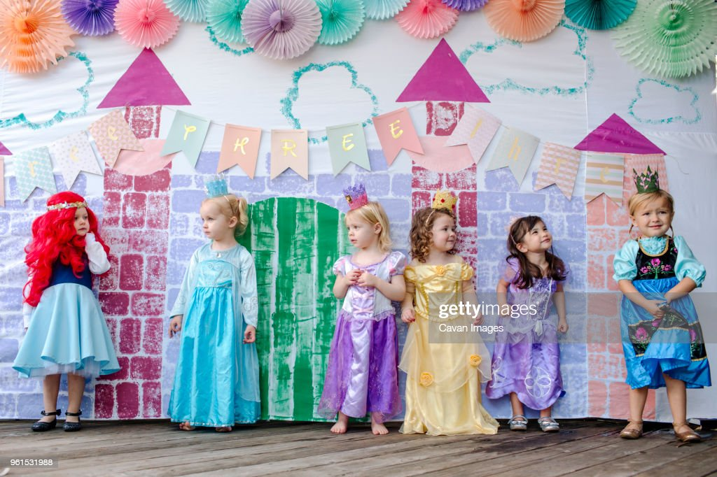 cute girls standing against castle painting during princess party