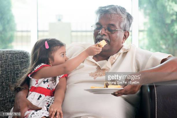 cute granddaughter feeding sweet bread to grandfather on couch at home - cute stock pictures, royalty-free photos & images