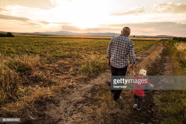 cute grandfather and grandson going for a walk - rear view photos stock photos and pictures