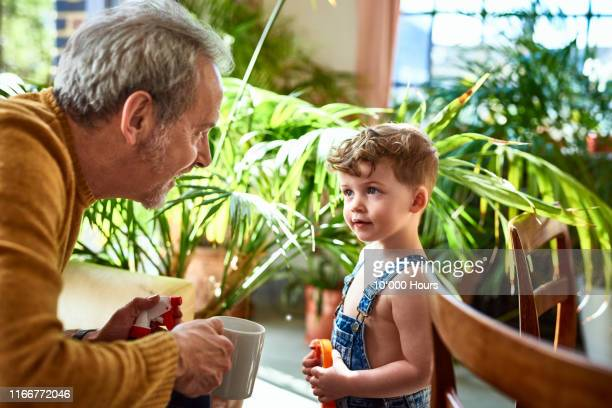 cute grandson face to face with grandfather - showing respect stock pictures, royalty-free photos & images