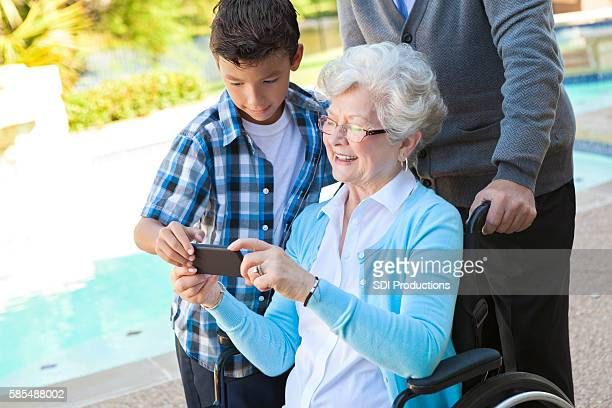 Cute grandson helps his grandparents with smartphone