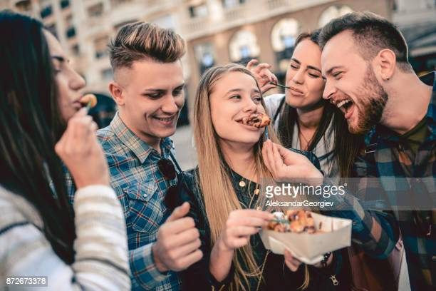 cute group of people eating donuts on fair in town square - eating utensil stock photos and pictures