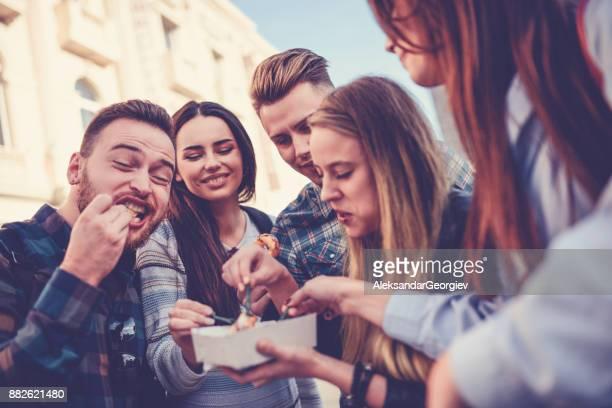 Lindo grupo de gente comiendo Donuts en feria en Plaza de la ciudad