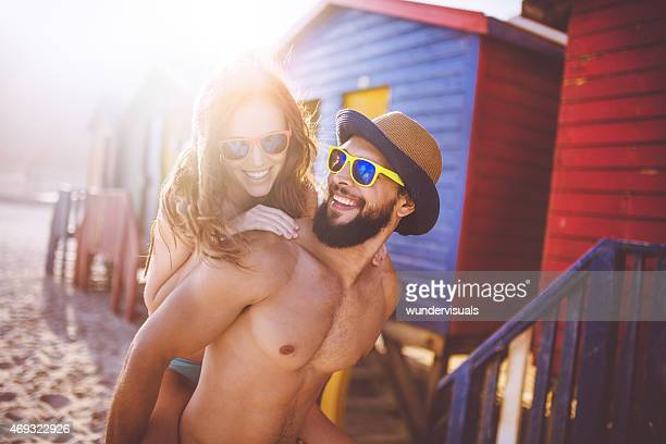 Cute guy piggybacking his girlfriend in front of beach huts