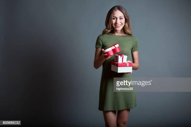 Süße glücklich Frau mit ein verpacktes Geschenk auf grauem Hintergrund