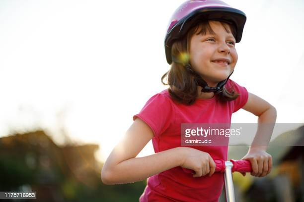 cute happy girl riding push scooter - damircudic stock photos and pictures