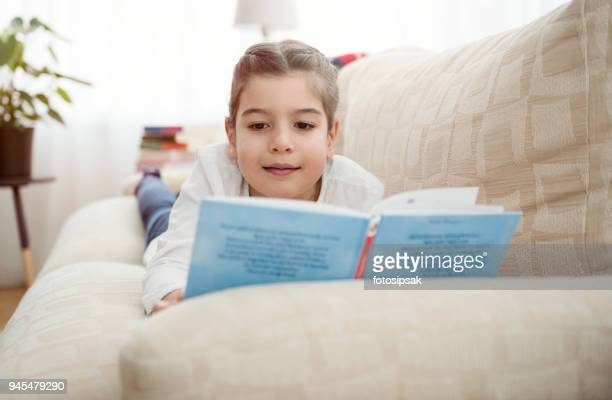 Cute happy little girl reading a child book at home