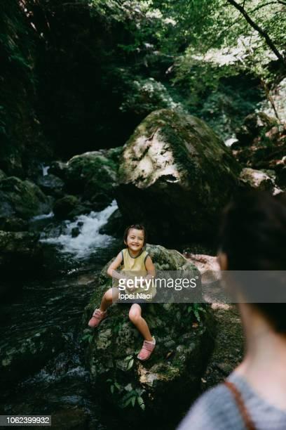 Cute happy little girl sitting on boulder in river, Japan