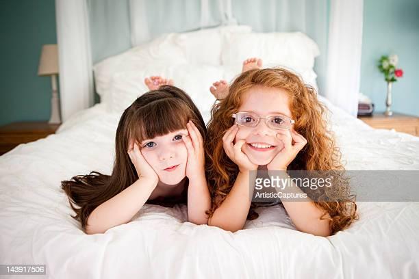 Niedlich, glücklich Schwestern liegen auf dem Bett zusammen im Schlafzimmer