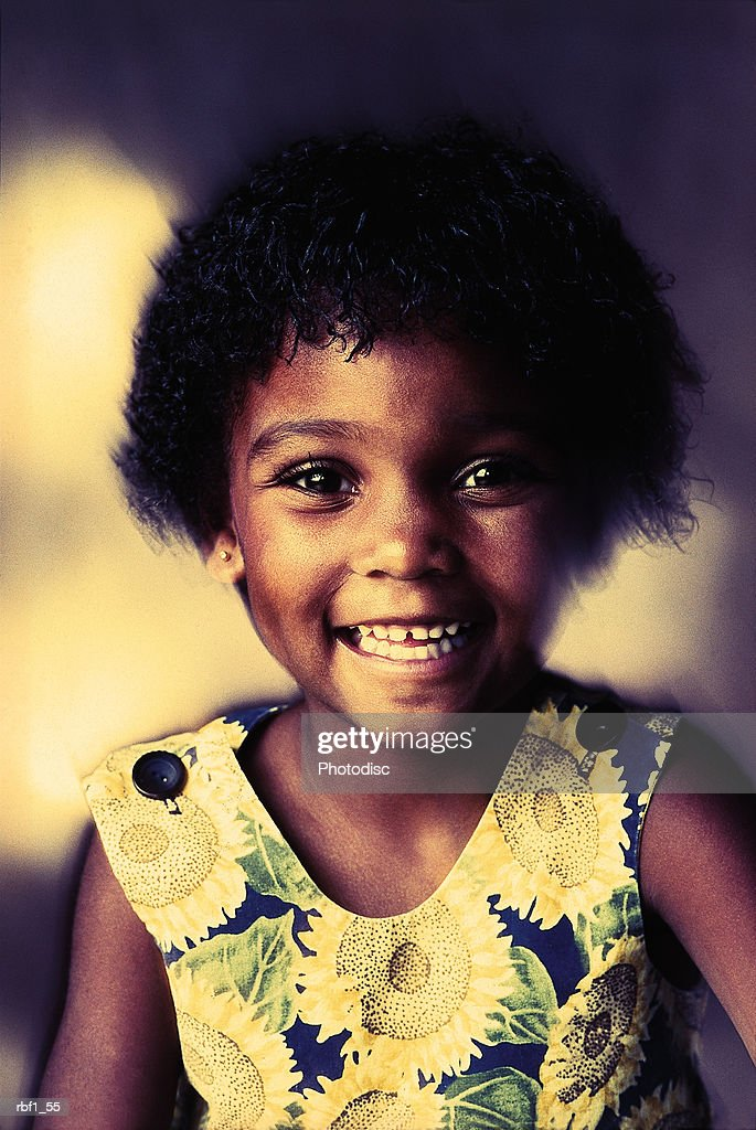 cute happy young african-american girl with short black hair and big brown eyes wearing a sleeveless sunflower dress smiles showing all of her little teeth : Stockfoto