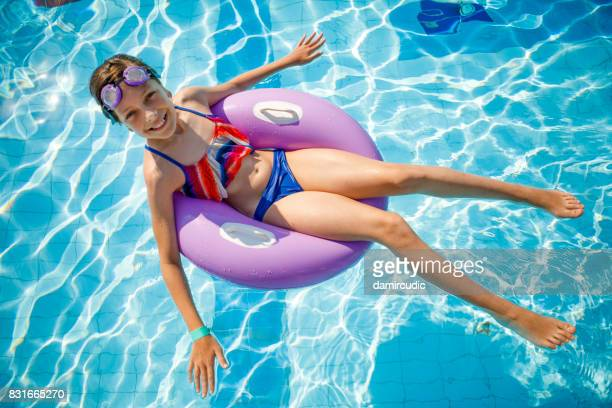 Cute happy young girl relaxing in swimming pool