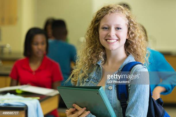 Cute high school age girl holding notebook in classroom