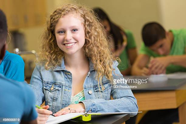 Cute high school student taking notes during science class