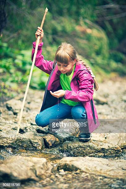 Cute hiker drinking water from moutain stream