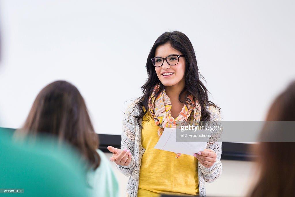 Linda hipster de estudante lendo relatório na frente dos colegas de turma com facilidade : Foto de stock