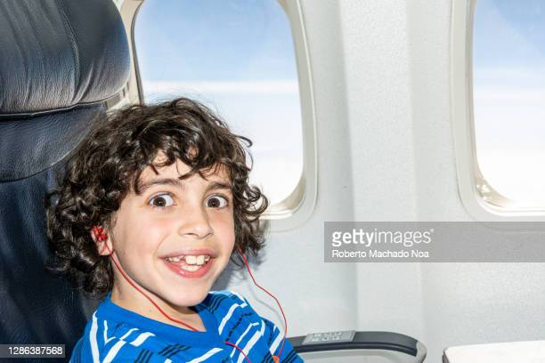 cute hispanic child boy in a plane - primary age child stock pictures, royalty-free photos & images
