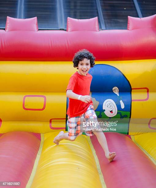 S SQUARE TORONTO ONTARIO CANADA Cute Hispanic child boy with curly hair playing in an inflatable playground during summer in Toronto