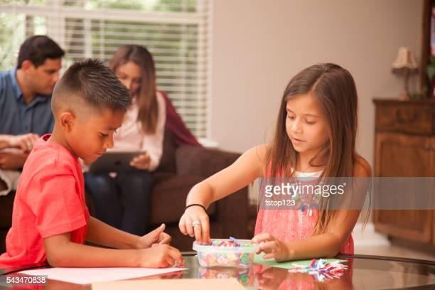 Mignon hispanique enfants à faire leurs devoirs à la maison ensemble.  Famille.