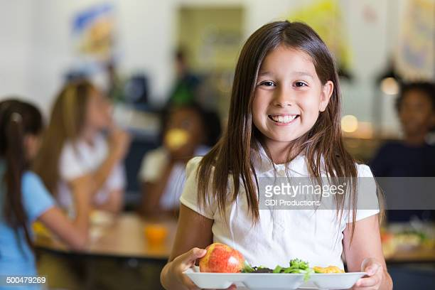 Cute Hispanic elementary school student holding tray of cafeteria food