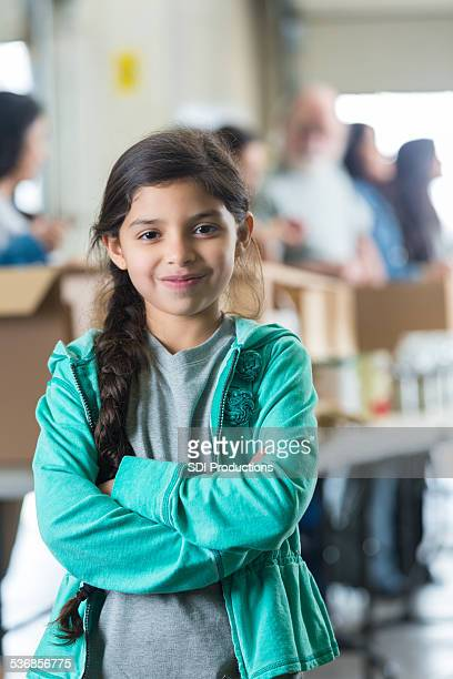 Cute Hispanic girl standing near volunteer donation sorting line