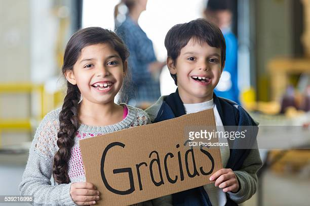 Cute Hispanic kids holding GRACIAS sign in food bank