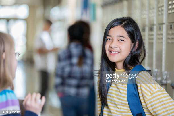 cute hispanic little girl smiles while standing in hallway of elementary school after class - junior high student stock pictures, royalty-free photos & images