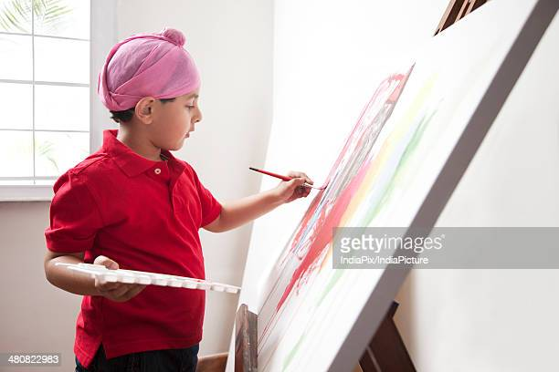Cute Indian boy painting canvas at art workshop