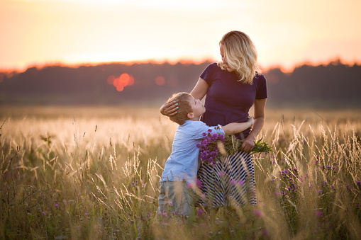 Cute kid boy hugging his mother on a summer meadow on beautiful summer sunset. Happy family together. Mum and child. Motherhood and childhood. Family walking in the field. Outdoors. 1144821535
