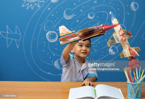 cute kid imagine space travel with set of infographics over textured wall background - school icon stock photos and pictures