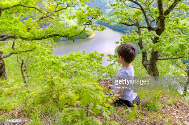 cute kid playing alone forest at