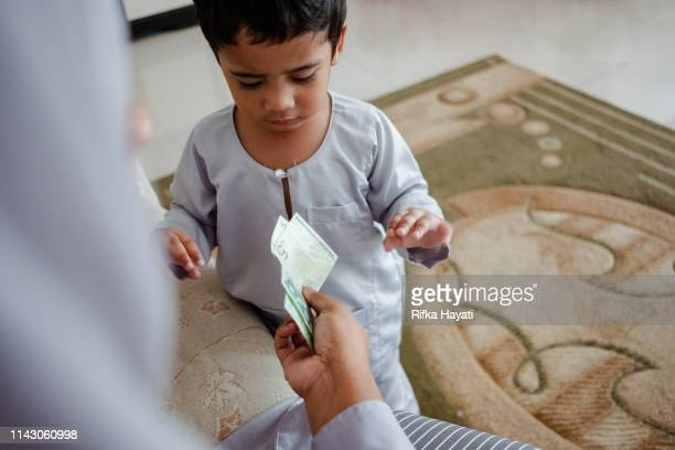 cute kid receiving green packet on eid mubarak - eid al adha stock pictures, royalty-free photos & images