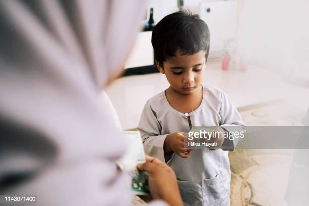 cute kid receiving green packet on eid mubarak - eid mubarak stock pictures, royalty-free photos & images