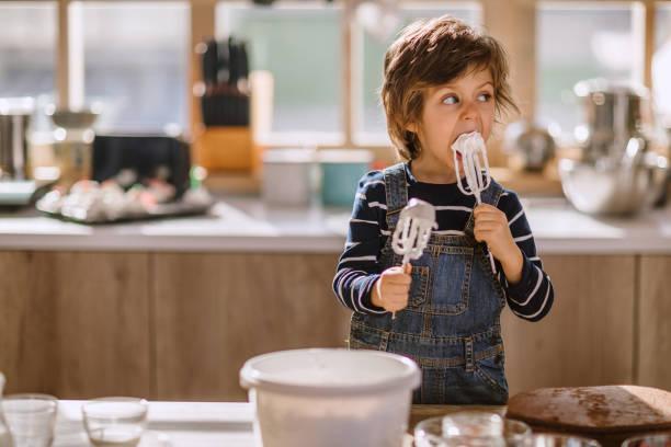 可愛的孩子品嘗打蛋者的鮮奶油 - 焗 預備食物 個照片及圖片檔