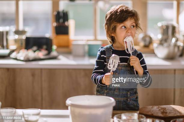 niedliche kid tasting whipped creme of egg beater - kochen stock-fotos und bilder