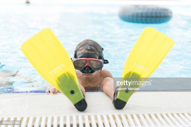 Cute kid with diving mask and flippers on pool