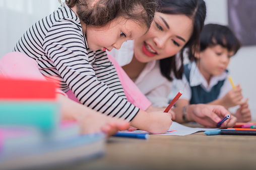 Cute kids and Asian teacher drawing in artist class. Back to school and education concept. Nursery and Preschool theme. Student and Baby sister theme. 954952668
