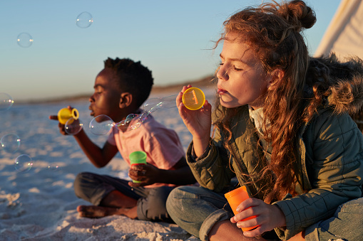 Cute kids blowing soap bubbles on the beach - gettyimageskorea