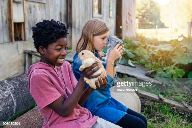 Cute kids cuddling baby rabbits outdoors in spring.
