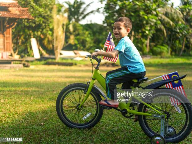 cute kids cycling with national flag - ibnjaafar stock photos and pictures