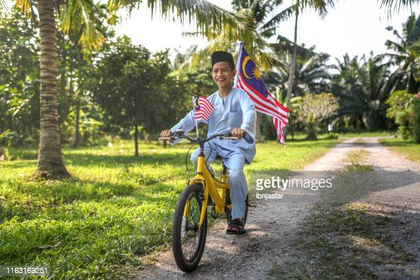 cute kids cycling with national flag - malaysia stock pictures, royalty-free photos & images