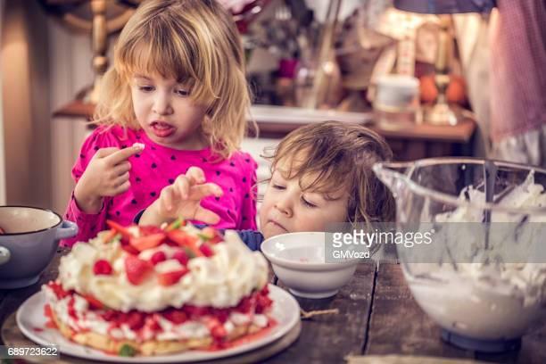 Cute Kids Eating Berry Pavlova Cake with Strawberries and Raspberries