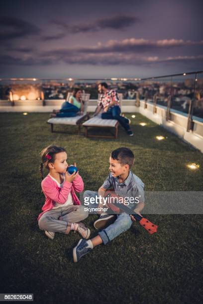 cute kids having fun on a penthouse terrace by night. - penthouse girl stock photos and pictures